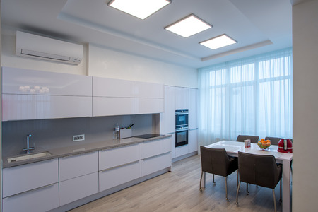 White kitchen with table and large windows Фото со стока