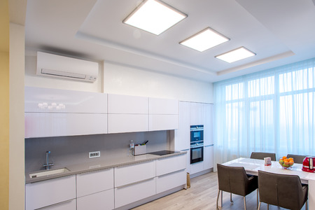 White kitchen with table and large windows Фото со стока - 75247216