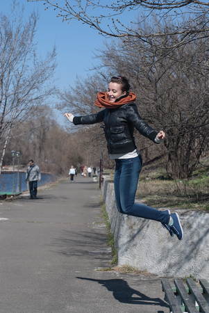 The young girl in jeans jumping fun Фото со стока