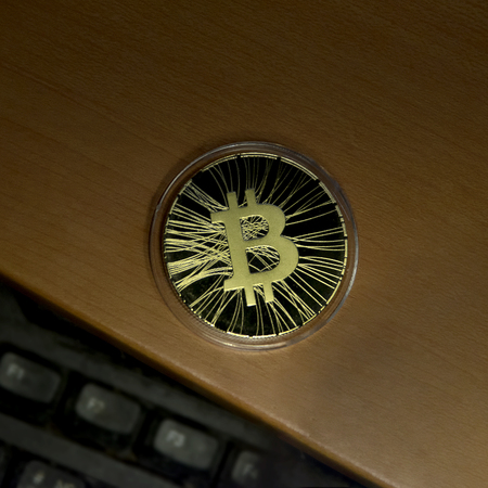 Bitcoin on the desk and keyboard dark