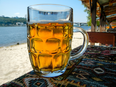 Cold beer mug with handle on table                                Фото со стока