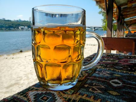 Cold beer mug with handle on table                                Stock Photo