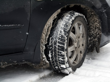 Dirty car tire with snow photo
