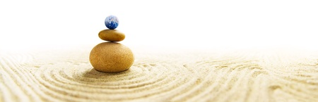 Stone pile in a Zen Garden with a miniature Earth globe as topmost stone photo