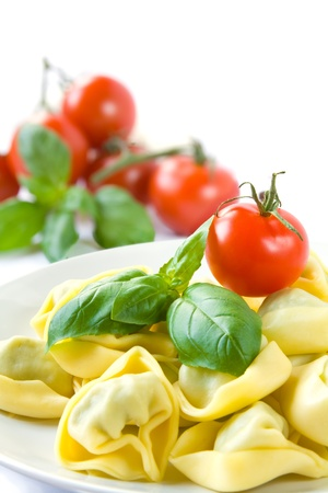stuffed tortellini: Tortellini served on a plate with basil leaves and tomatoes Stock Photo