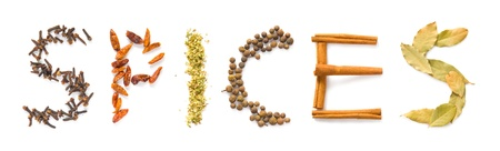 The word spices written in letters of clove, hot peppers, oregano, allspice, cinnamon sticks and bay leaves photo
