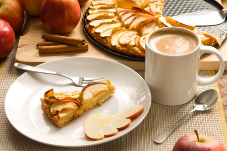 Fresh baked home made apple pie served on a white plate with coffee photo