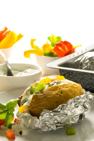 foil: Baked potato with sour cream, herbs and pepper Stock Photo