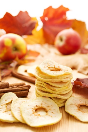 dry fruits: Dried apples with cinnamon and autumn leaves Stock Photo
