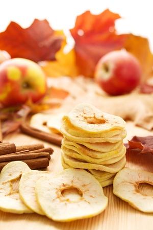frutas secas: Manzanas secas con la canela y las hojas de otoño