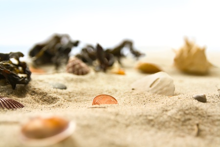 cent: One cent euro coin in the sand of a beach