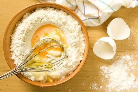 Eier und Mehl mit einem Schneebesen in einer braunen Schüssel gemischt