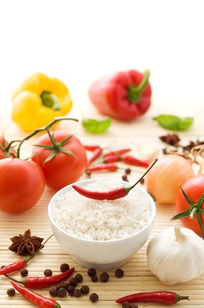 Bowl of uncooked rice with ingredients and spices photo