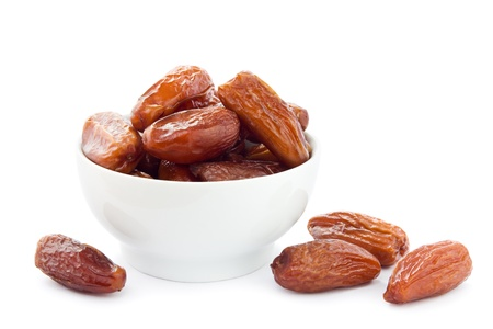 dry fruit: Dates in a white bowl on a white background