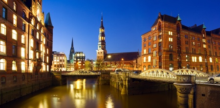 ware house: Warehouse district   Speicherstadt   of Hamburg at night with view towards the city center