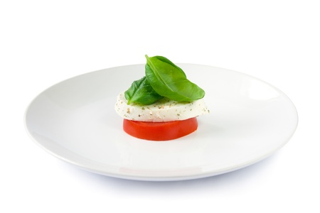 Simple small caprese salad with tomato, mozzarella cheese and basil leaves photo