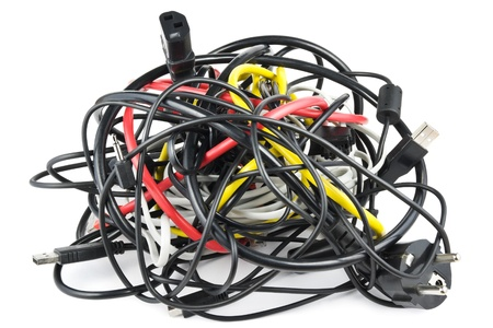 knotted: Big chaotic knot of mixed cables on white  Stock Photo