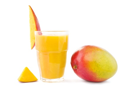 Big glass of mango smoothie with a mango