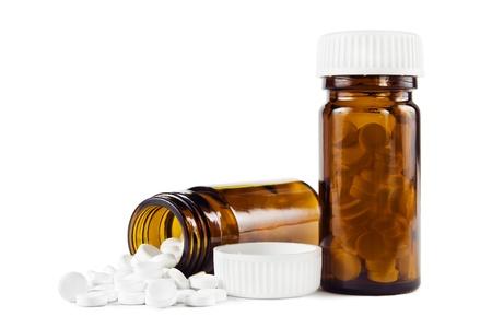 Weiße Pillen in zwei Glasflaschen auf weißem Hintergrund