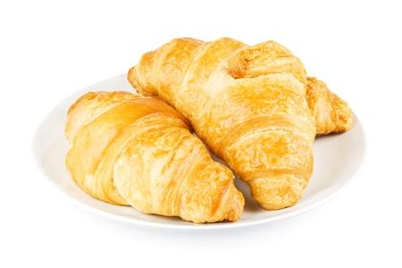 Croissants frais sur une plaque sur un fond blanc