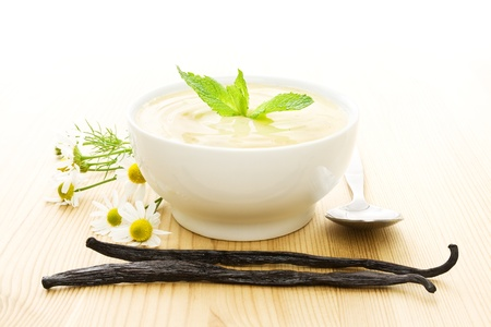 White bowl of vanilla yogurt with vanilla beans, flowers and a spoon on wood