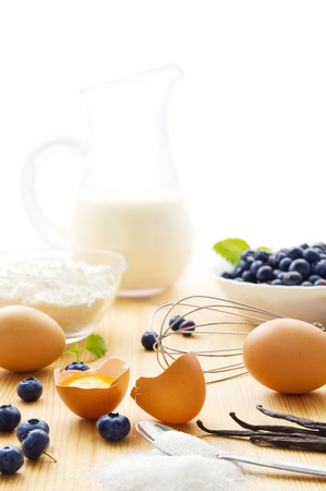 starch: Ingredients for a homemade vanilla pudding with blueberries, fresh eggs, sugar, vanilla beans, a jug of milk, and a bowl of corn starch