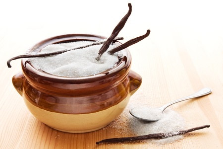 sugar bowl: Brown bowl with white vanilla sugar, vanilla beans and a spoon on wood