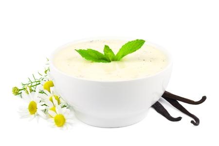 flor de vainilla: Taz�n de fuente de yogur de vainilla con vainas de vainilla y flores de margarita en blanco Foto de archivo