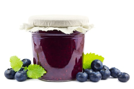 Jar with blueberry jam, decorated with fresh blueberries and balm leaves on white