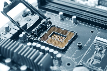 computer chip: Empty cpu processor socket on a computer motherboard with pins visible  Blue toned