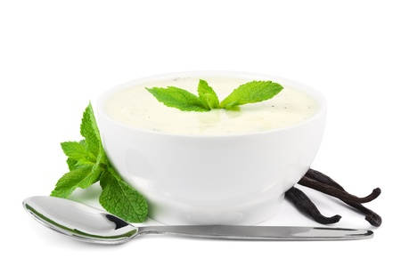 Vanilla yogurt with mint leaves, vanilla pods, and a spoon on white