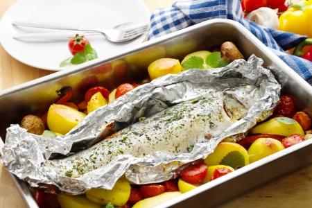 Gebackene Forelle gewickelt einer Aluminiumfolie mit Gemüse in eine Auflaufform