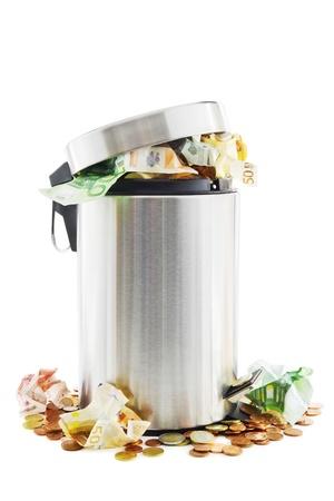 cesto basura: Residuos concepto de dinero con el dinero en y alrededor de un cubo de basura en blanco