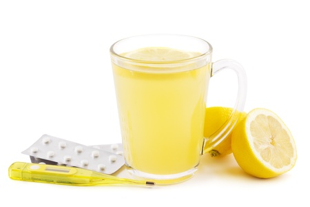 Hot lemon drink as home remedy concept with clinical thermometer and pills on white photo