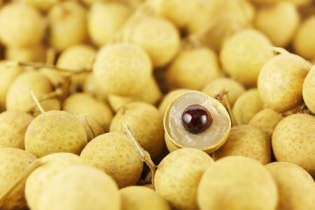 longan: Full frame image of large group of thai longans  Small depth of field with focus on the peeled half longan