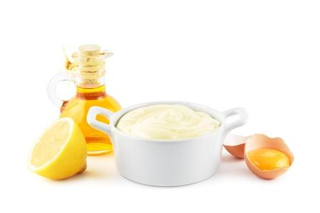 mahonesa: Tazón de mayonesa con los ingredientes principales, el aceite, los huevos y los limones Foto de archivo