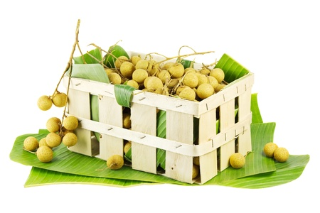 longan: Longans in a fruit crate on banana leaves isolated on white