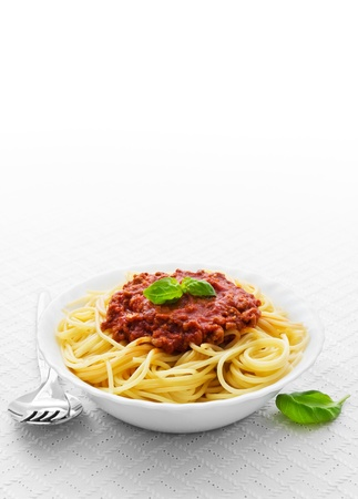pasta fork: Bowl of spaghetti bolognese with fork and spoon on a white tablecloth