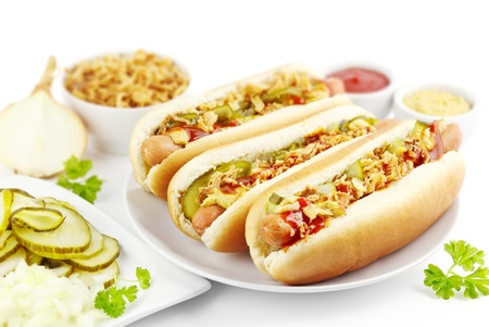 onions: Three hot dogs with ingredients on a plate