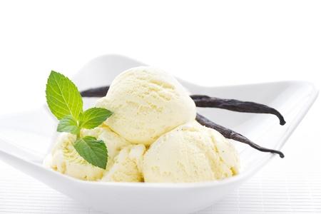 postres: Helado de vainilla con vainas de vainilla en un recipiente blanco Foto de archivo
