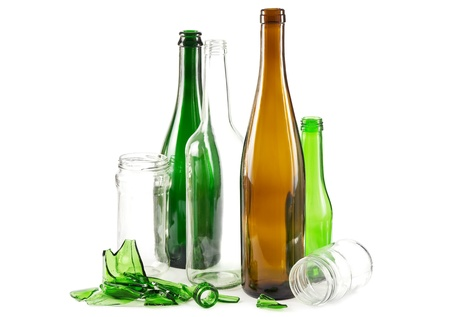 Glass waste with mixed bottles in green white and brown and empty glass jars