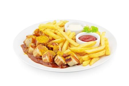 Currywurst met frieten op wit Stockfoto