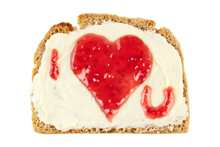 Heart shape with a love message made of red jam on a slice of bread, isolated on white photo