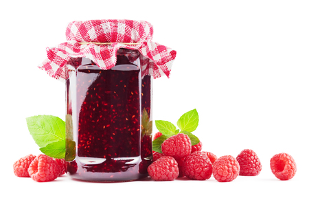 Jar with raspberry jam with raspberries on white.