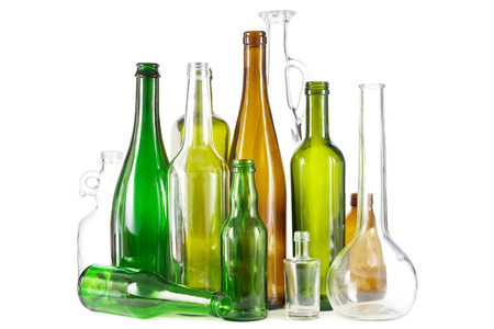 Group of mixed colored glass waste bottles on white.