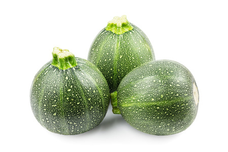 Three round zucchini on a white background
