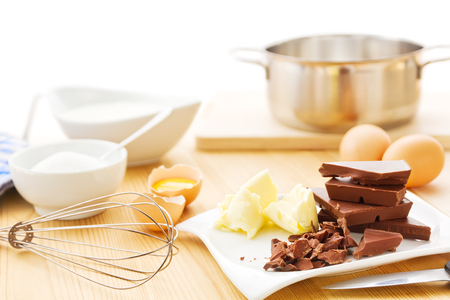 Ingredients for a mousse au chocolat including dark chocolate, eggs, butter, cream and sugar.