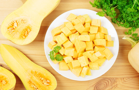 butternut squash: Plate with diced butternut squash and butternut squashes on a wooden background. Stock Photo