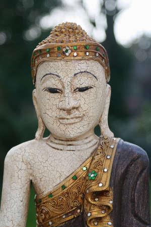 pokrývka hlavy: Wooden buddha with golden headgear and sparkling stonesofdbedekking en flonkerende steentjes