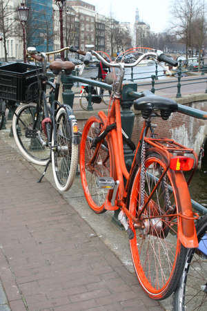 citytrip: Orange colored bike along a canal in Amsterdam Stock Photo